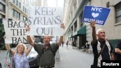 """纽约,旅行禁令的支持者们举着""""让叙利亚人滚出去""""的标语牌回应反旅行禁令的抗议人群。(2017年6月29日)"""
