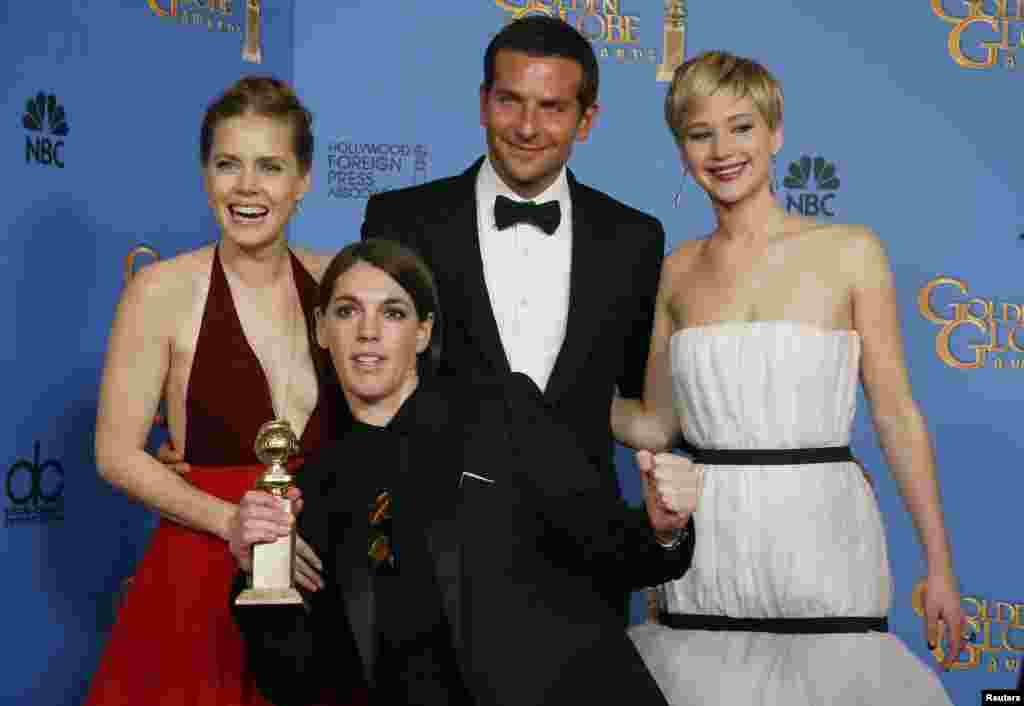 """American Hustle"" stars Amy Adams, Bradley Cooper and Jennifer Lawrence pose with producer Megan Ellison after the film won the award for Best Motion Picture, Musical or Comedy at the Golden Globe Awards, Jan. 12, 2014."