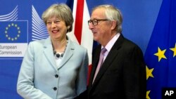 British Prime Minister Theresa May is greeted by European Commission President Jean-Claude Juncker before a meeting at EU headquarters in Brussels, Dec. 8, 2017. May and Juncker met early Friday morning following crucial overnight talks on the issue of the Irish border.