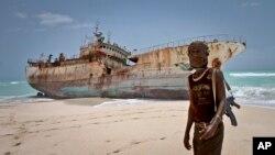 Dalam foto tertanggal 23/9/2012 ini seorang perompak Somalia berdiri di depan kapal Taiwan yang terhempas ke pantai di daerah Hobyo, Somalia.