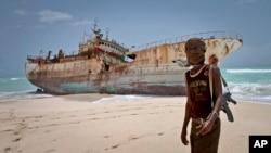 지난해 9월 소말리아 호비오 해변에서 한 해적이 납치됐다가 방치된 선박 앞에 서있다.