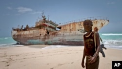 FILE - A masked Somali pirate stands near a Taiwanese fishing vessel that washed up on shore after the pirates were paid a ransom and released the crew, in the once-bustling pirate den of Hobyo, Somalia, Sept. 23, 2012.