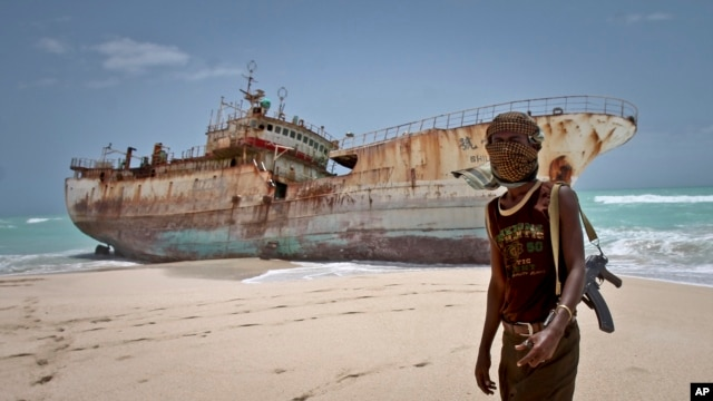 FILE - A masked Somali pirate stands near a Taiwanese fishing vessel that washed up on shore after the pirates were paid a ransom and released the crew, in Hobyo, Somalia, September 2012.