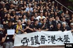 約100名港大校友及社會人士在港大校園集會,以手語表達「守護港大」。(美國之音湯惠芸)