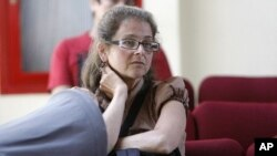 FILE - Lori Berenson sits in a migration office in Lima. Berenson was sentenced to life in prison for helping the Tupac Amaru leftist rebel group plan an armed takeover of Congress.