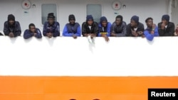Migrants wait to disembark from Aquarius in the Sicilian harbour of Catania, Italy, May 27, 2018.