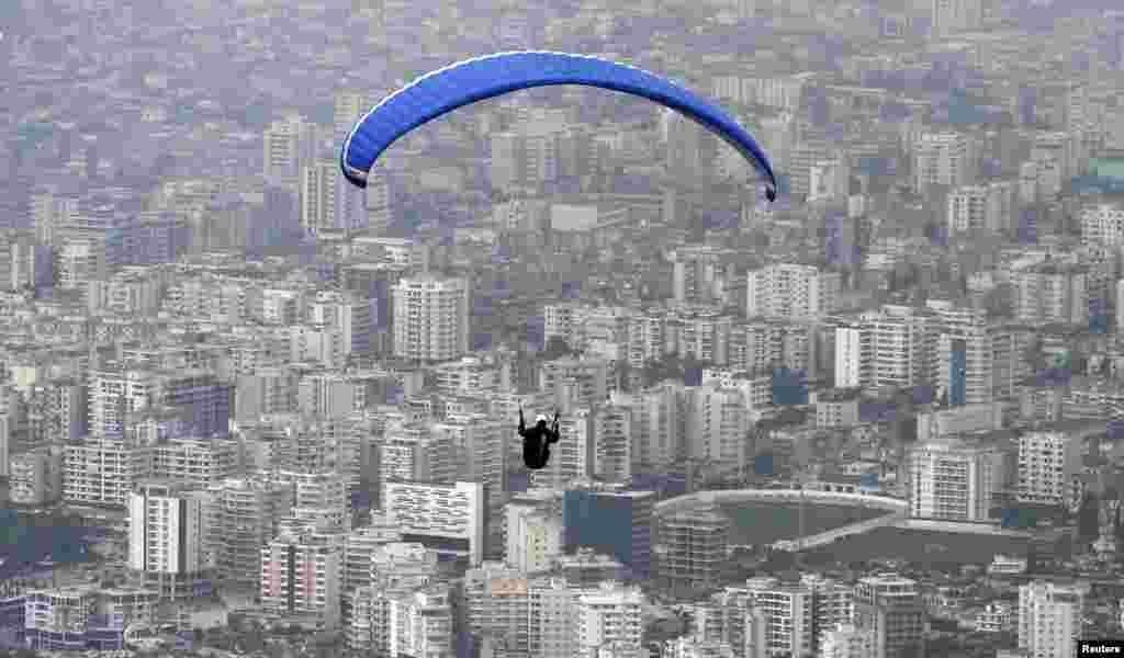 A paraglider flies over the city of Vlorë during the annual Balkan paragliding competition, some 150 km (94 miles) from Tirana, Albania.