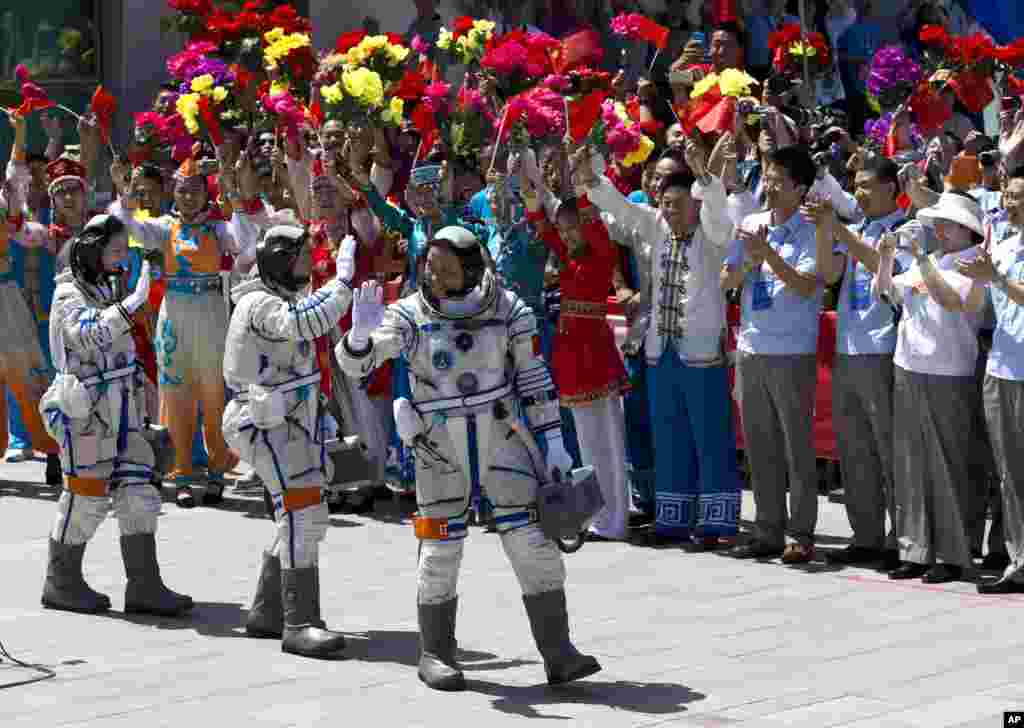 China's astronauts from left, Wang Yaping, Zhang Xiaoguang and Nie Haisheng wave as they leave the Jiuquan satellite launch center near Jiuquan in western China's Gansu province. Three astronauts took flight aboard the spacecraft to the dock with China's Tiangong 1 space lab.