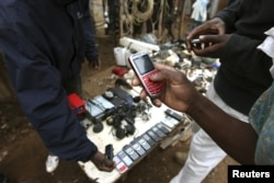 FILE - A vendor hawks secondand mobile phones at the sprawling Kibera slum, one of the largest and poorest slums in Africa, near Kenya's capital, Nairobi, Aug. 26, 2011.
