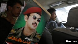 A poster of Ahmed Ali Abdullah Saleh, the son of Yemen's former President Ali Abdullah Saleh, is pictured inside a car of a supporter during a demonstration to demand for presidential elections to be held and for him to run for presidency in Sana'a, March 10, 2015.