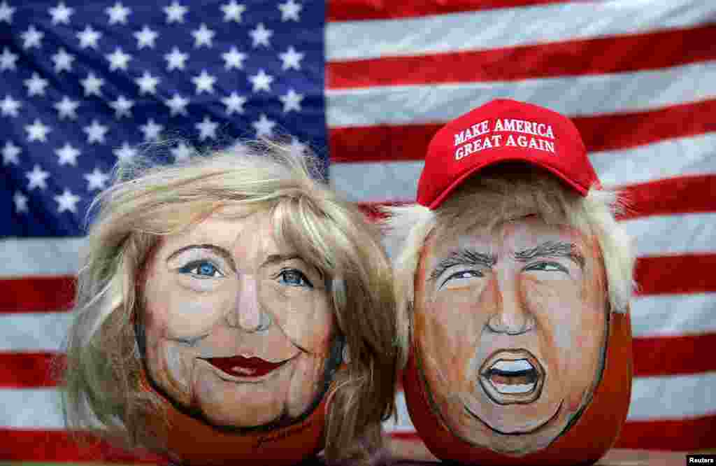 The images of U.S. Democratic presidential candidate Hillary Clinton (L) and Republican Presidential candidate Donald Trump are seen painted on pumpkins created by artist John Kettman in LaSalle, Illinois, June 8, 2016.