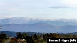 The Great Smoky Mountains rise in the background about 20 miles away from this Knoxville, Tenn., neighborhood on Thursday, March 10, 2005.