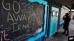 在一間已經關閉的餐館門口的黑板上,寫著希望颶風離開的文字。