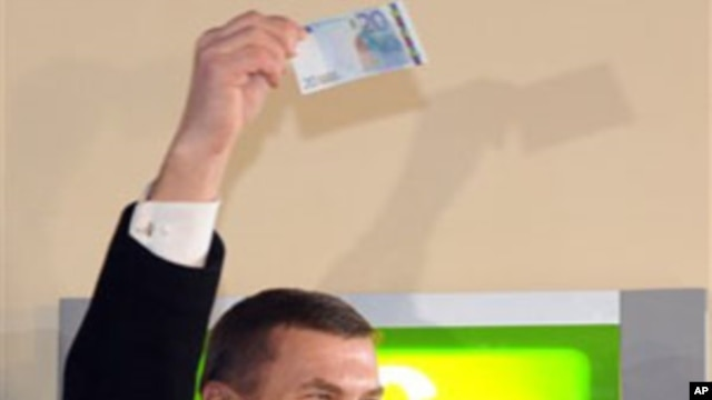 Estonia's Prime Minister Andrus Ansip, lifts a 20 Euro banknote which he withdrew from an ATM cash machine in Tallinn, 01 Jan 2011