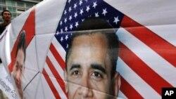 ایک آدمی جکارتہ میں 19 مارچ 2010 کو صدر اوباما کے حامیوں کی طرف سے نکالے جانے والے جلوس میں اوباما کی تصویر والا بینر اٹھائے کھڑا ہے