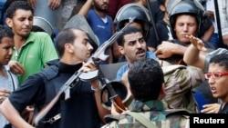 Polisi dan pendukung pemerintah Mesir di luar masjid al-Fatah di Kairo (17/8). (Reuters/Muhammad Hamed)