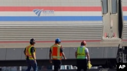 Workers walk past a baggage car, Sept. 27, 2021, from an Amtrak train that derailed Saturday, near Joplin, Mont.