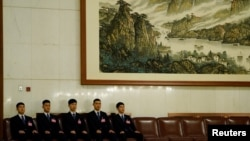 2018年3月18日在北京人民大会堂举行的全国人民代表大会全体会议上,安全人员坐在他们的座位上,姿势整齐划一。