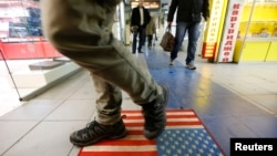 FILE - A man steps on a doormat depicting a U.S. flag, inside a shopping center in Moscow, Russia, Dec. 25, 2014.