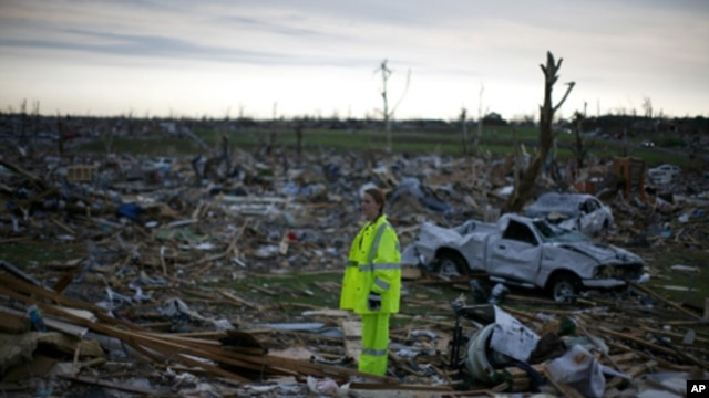 A volunteer stands in a destroyed neighborhood in Joplin, Missouri on May 27, 2011.