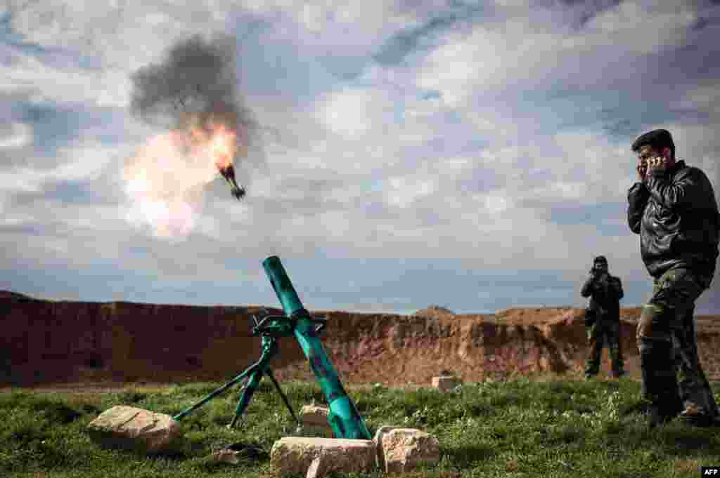 Syrian rebels fire a mortar toward regime forces stationed at Kwiriss airport in Al-Bab, 30 kilometers from the northeastern Syrian city of Aleppo.