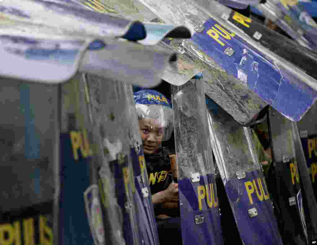 A riot police officer peeks through shields following a clash with protesters marching towards the parliament in suburban Quezon city, northeast of Manila, where Philippine's President Benigno Aquino delivers his final state of the nation address.