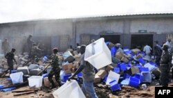 Guinean soldiers remove boxes filled with electoral materials from a warehouse on fire in a military camp in Conakry.