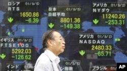 A man walks by an electronic stock board of a securities firm in Tokyo, September 5, 2011.