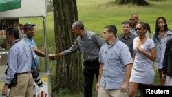 Presiden AS Barack Obama, tengah, berjabat tang an dengan seorang pedagang ketika berjalan-jalan di Central Park dengan anaknya Sasha, kedua dari kanan, dan Malia, kanan, di New York, 18 Juli 2015.