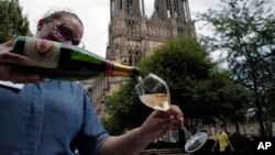 A waitress serves a glass of champagne at La Grande Georgette restaurant in front of the cathedral in Reims, the Champagne region, east of Paris, Tuesday, July 28, 2020. (AP Photo/Francois Mori)