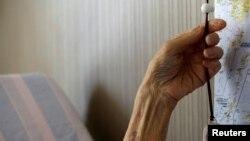 Katsuo Saito, pasien Leukemia berusia 89, memegang alarm yang bisa mengirimkan peringatan ke sebuah perusahaan keamanan yang mengawasi manula di Tokyo, Jepang, 8 September 2017.