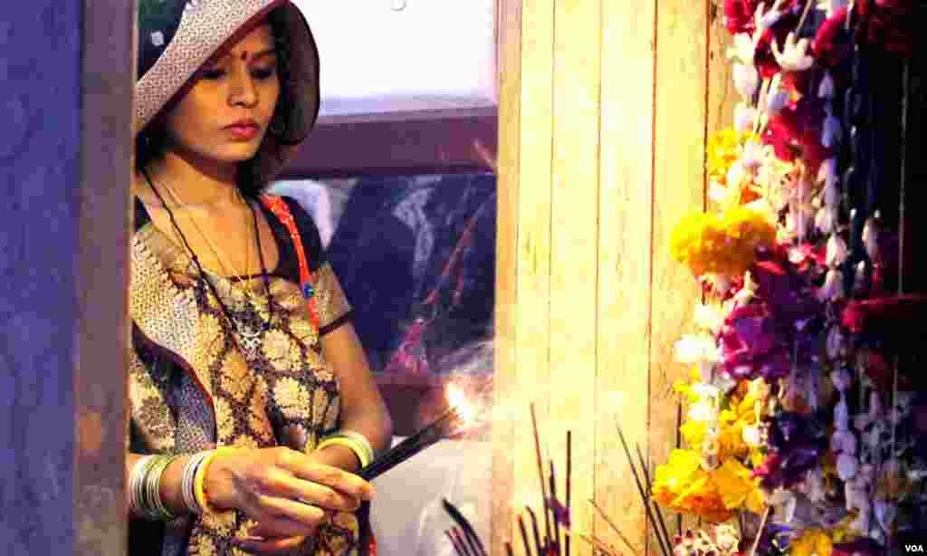 کراچی میں ہندو برادری کے تہوار 'شیوراتری' کے موقع پر ایک خاتون مندر میں پوجا کرتے ہوئے