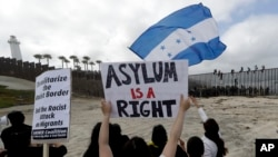 Di dân Trung Mỹ ngồi trên bức tường biên giới trên bãi biển ở San Diego trong cuộc tập họp các di dân sống ở hai bên biên giới (ảnh chụp ngày 29/4/2018)