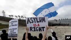 """Migran ki nan karavàn santwo-ameriken an pote yon pannkat ki di an anglè """"Azil se yon dwa (de lòm)""""..."""