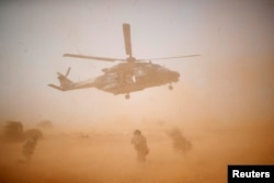 FILE - A NH 90 Caiman military helicopter takes off during the regional anti-insurgent Operation Barkhane in Inaloglog, Mali, Oct. 17, 2017.