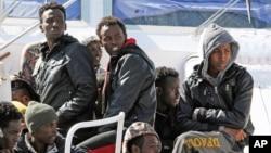 Sebagian imigran yang berhasil diselamatkan duduk di atas kapal Italia di pelabuhan Messina (18/4).