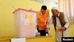 Seorang pria mencelupkan jarinya ke dalam tinta sebelum memberikan suaranya dalam pemilu parlemen di Al Bayda, Libya (25/6).