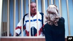 FILE - Sergei Skripal is seen behind bars on a screen of a monitor outside a courtroom in Moscow, Aug. 9, 2006.