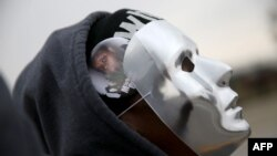 Một người biểu tình đeo mặt nạ có hình của Michael Brown khi cô cùng những người khác chờ đợi quyết định của đại bồi thẩm đoàn hôm 15/11 gần Ferguson, Missouri.