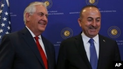 U.S. Secretary of State Rex Tillerson, left, and Turkey's Foreign Minister Mevlut Cavusoglu stop for photographers prior to their meeting in Ankara, March 30, 2017.