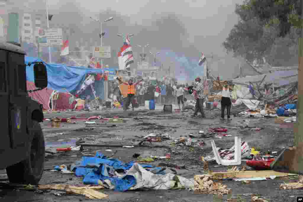 Supporters of ousted Islamist President Mohammed Morsi, stand among debris and smoke in background as they confront Egyptian security forces trying to clear the smaller of the two sit-ins, near the Cairo University campus in Giza, Cairo, Egypt, Wednesday,