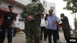 Seorang Uighur sedang menjelaskan kepada polisi Tiongkok mengenai alasan mengapa dia berjualan melon di Kashgar, selatan propinsi Xinjiang saat Ramadan, Agustus lalu (foto:dok).