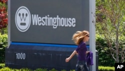 FILE - A woman walks past the sign marking the entrance to the Westinghouse International Headquarters on May 19, 2014, in Cranberry, Pa.