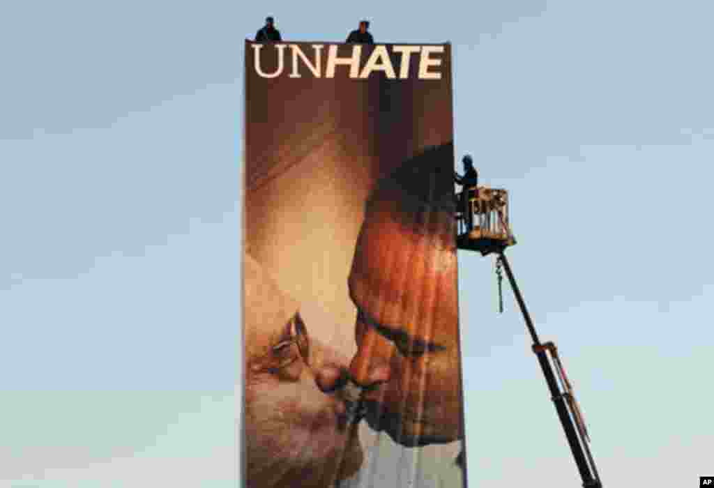 Workers install a Benetton billboard advertisement showing a composite image of Israeli Prime Minister Benjamin Netanyahu (R) kissing Palestinian President Mahmoud Abbas in Tel Aviv November 28, 2011. The image, part of a series of pictures of world leade