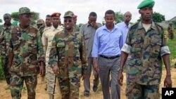 Somalian President Sharif Sheikh Ahmed [2nd L with stick] walks with officials and army commanders of the Somalian transitional government at the front line in Deynile district, in Somalia's capital Mogadishu, October 24, 2011.