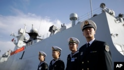 FILE - In this Dec. 7, 2016, photo, Chinese Navy officials stand in front of the ship Daqing, in San Diego. For the second year in a row, China has said it would increase its defense spending by a single-digit percentage.