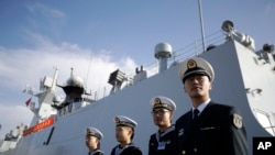 In this file photo from Dec. 7, 2016, Chinese navy officials stand in front of the ship Daqing, in San Diego, CA.