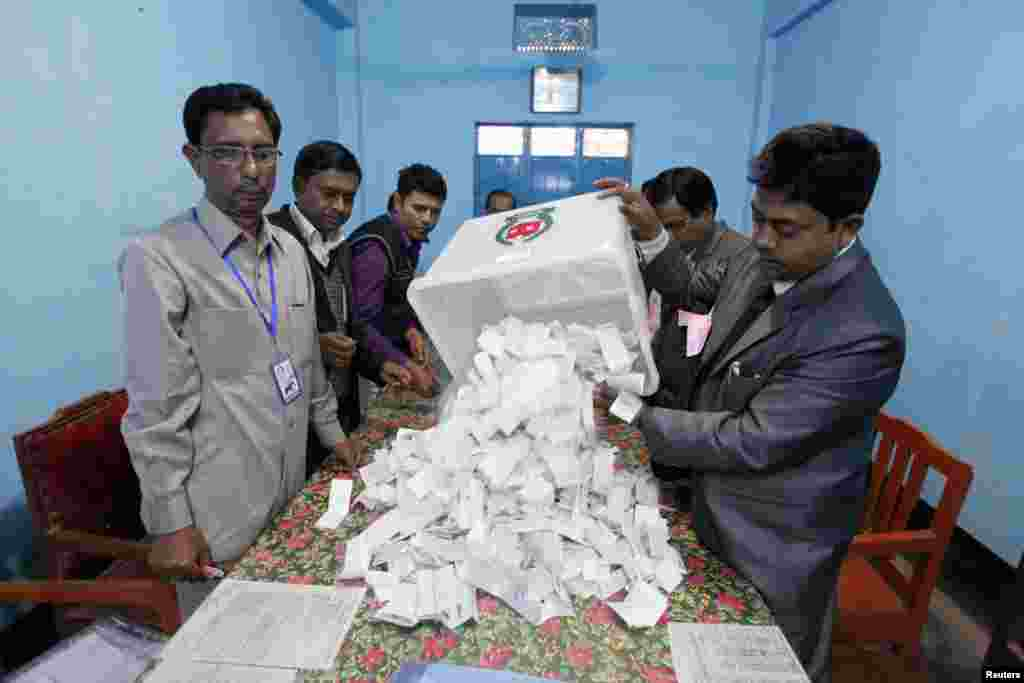 A polling officer pours ballot papers from a box onto a table to count during parliamentary elections in Dhaka, Jan. 5, 2014.