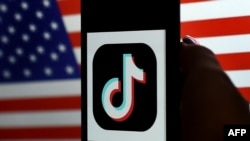 In this photo illustration, the social media application logo, TikTok is displayed on the screen of an iPhone on an American flag background on August 3, 2020 in Arlington, Virginia. - President Donald Trump said Monday that Chinese-owned hugely popular v