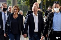 German Finance Minister, vice-chancellor and the Social Democratic SPD Party's candidate for chancellor Olaf Scholz (C) and his wife Britta Ernst (2nd L) arrive at the polling station in Potsdam, eastern Germany, Sept. 26, 2021.